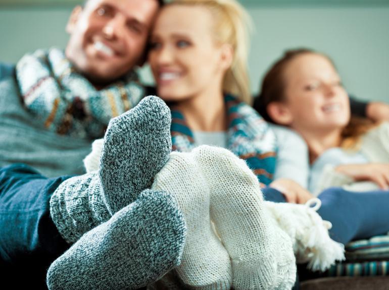 perhe istuu sohvalla villasukat jaloissa